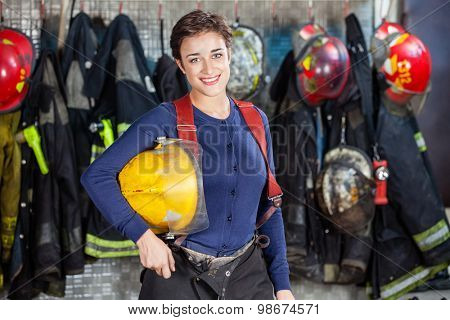 Portrait of happy firewoman holding helmet while standing at fire station