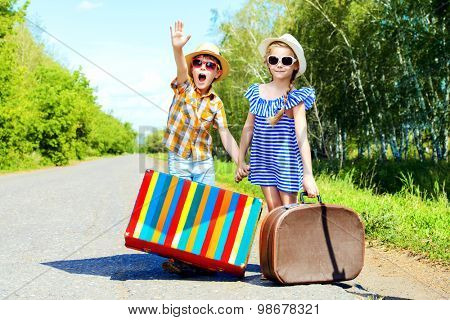 Two happy kids catche a passing car near the road. Adventure and travel. poster