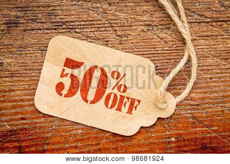 fifty  percent off discount  - a paper price tag against rustic red painted barn wood