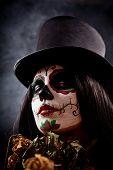 Sugar skull girl in tophat holding dead roses studio shot poster