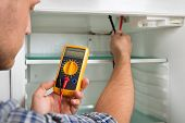 Young Male Technician Checking Fridge With Digital Multimeter poster