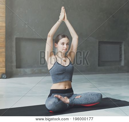 Attractive girl practicing yoga sitting in padmasana. Young woman in lotus pose doing breathing exercise on mat at sport club interior, copy space