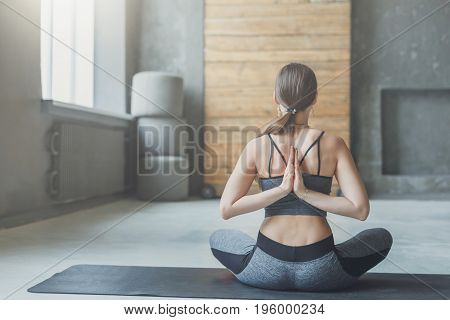 Young woman in yoga class making asana exercises. Girl do Reverse Prayer Pose, back and shoulders stretching. Healthy lifestyle in fitness club.