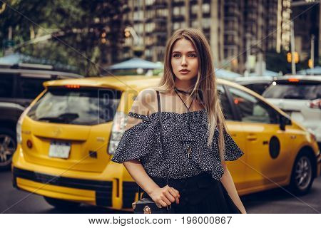 Beautiful young adult elegant woman came out from the taxi and walking in New York City street wearing summer clothes.