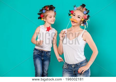 Funny family Mother and her child daughter girl with a paper accessories. Beauty funny girl holding paper star on stick. Beautiful young woman holding paper mustache on stick.