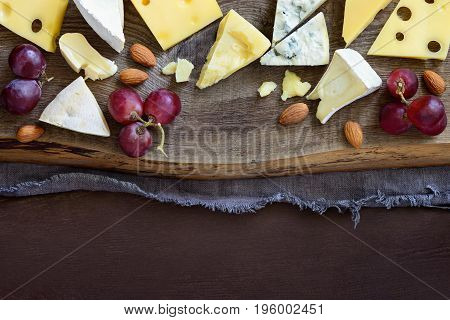 Various kinds of cheese such as brie blue cheese chadder and other set on a rustic table board view from above flat lay space for a text
