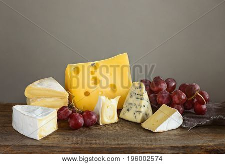 Cheese in assortment. Various kinds of soft artisan aged brie cuts blue cheese and Maasdam on a wooden board.