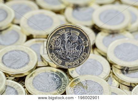 Heap Of Money And Back Of One Pound Coin.