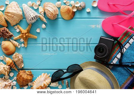 Vacation background on blue wood, top view with copy space. Beach accessories, flip flops, sunglsses, photo camera and seashells