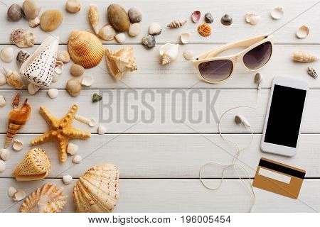 Vacation background on white wood, top view with copy space. Shopping online on smartphone.
