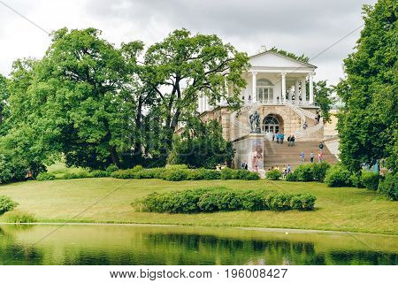 Pushkin, Russia - July 07, 2017 - Antique gallery in royal Catherine park in suburb of Saint Petersburg. Trees, lawn, coast of a lake. Summer landscape with nice park for prints, posters, interior.