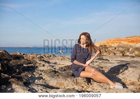 pretty girl sits on the rocky beach enjoys sunshine