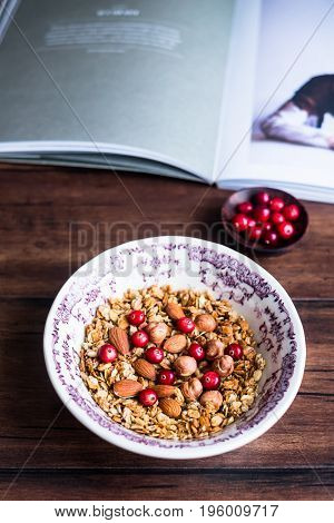 Homemade granola or muesli with fresh cranberry, almonds, hazelnuts in a bowl, selective focus