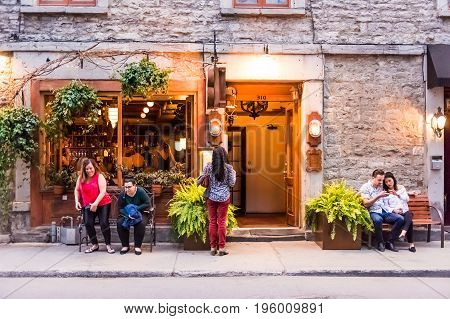 Montreal, Canada - May 27, 2017: Old Town Area With People Sitting On Sidewalk Street Benches By Res