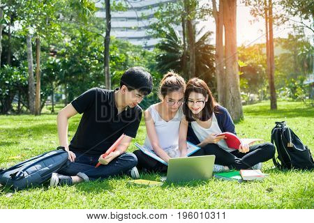 Young Student Asian Group Teenager with school folders on grass at university campus college
