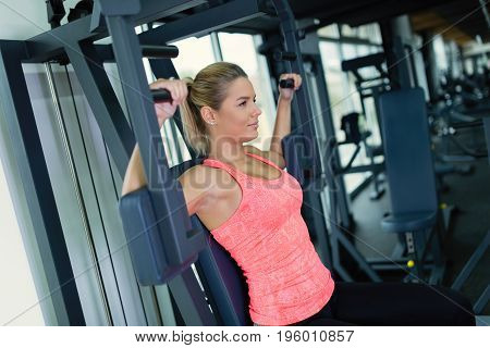 Beautiful young woman doing exercises for chest in gym