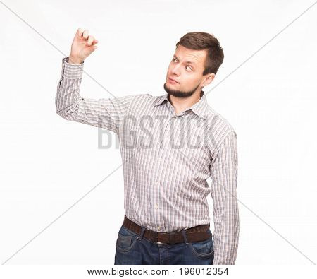 Young surprised man portrait of a confident businessman showing presentation, pointing paper placard gray background. Ideal for banners, registration forms, presentation, landings, presenting concept.