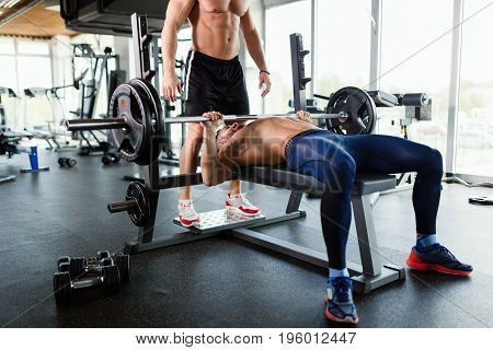 Handsome young muscular man doing bench press and gets help from friend