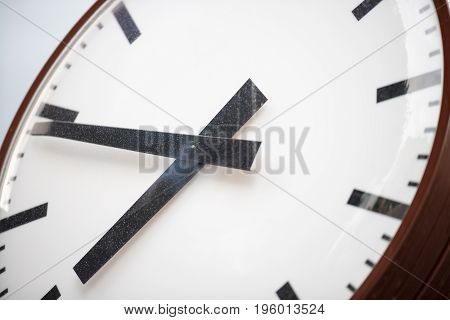Retro clock with hour and minute hands close-up. Old white dial with black stripes instead of numbers.