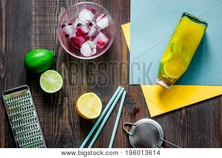 Bottle of fresh lemonade, fruits and ice cubes on wooden background top view.