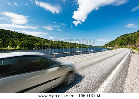 White car on country road in Norway Europe Scandinavia. Auto travel on sunny day. Blue sky with clouds.