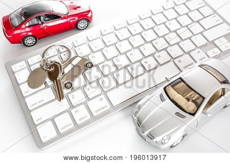 Buying car. Car keys on keyboard on white background top view.