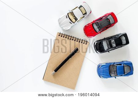 Buying car. Toy cars on white background top view.