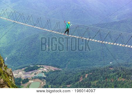 A Tourist In A Helmet And Safety Ropes Is At The Stretched Over The Abyss Between The Cliffs, Rope L