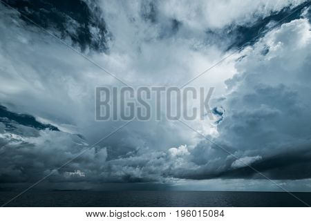 Dark clouds in open ocean. Tropical hurricane and sea storm