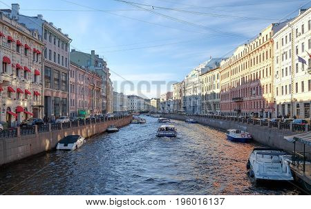 SAINT - PETERSBURG RUSSIA - MAY 23 2017: Tourists in the excursion boat sail on The River along the embankments in sunset time. And the good weather.