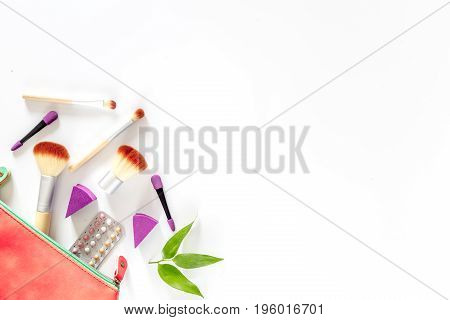 Cosmetic bag with contraceptives on white table background top view.
