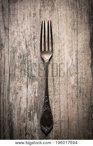 Old antique fork on dark wooden background.