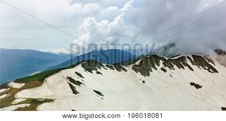 Panorama Of Snow-covered Aibga Ridge In Cloudy Summer Day
