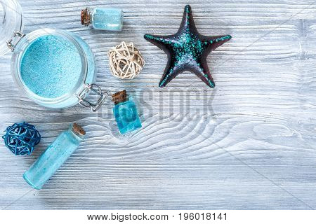 Dead sea cosmetics. Sea salt, blue clay and lotion on grey wooden table background top view.