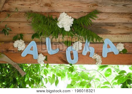 Aloha on wooden background, party Hawaiian-style, green thickets, Hawaiian background