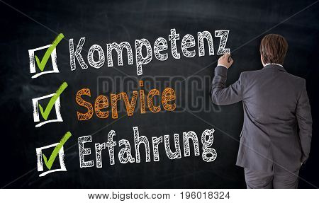Businessman Writes Kompetenz, Service, Erfahrung (in German Competence, Service, Experience) On Blac