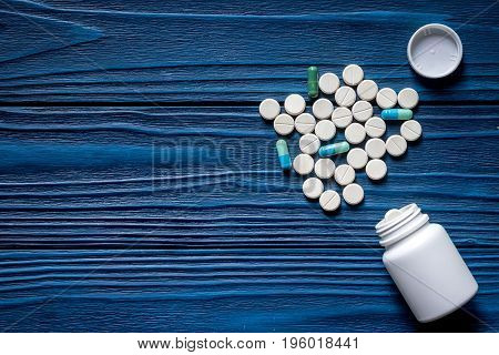 Drug therapy. Pills and pill bottle on blue wooden table background top view.