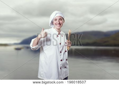 Nice Young Woman Chef With Thumb Up And Wood Utensils