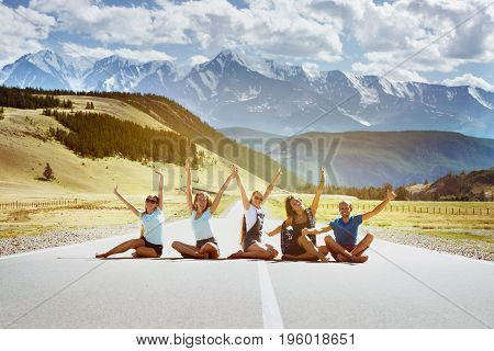 Group of five happy friends having fun sitting on the straight road on mountains background. Team or friendship concept