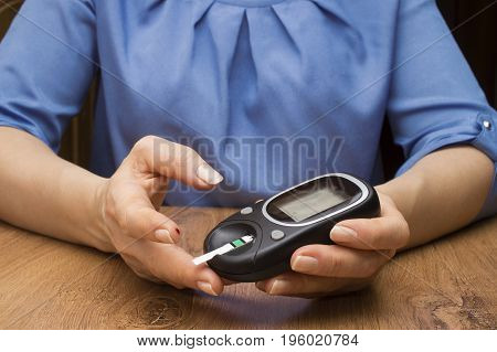 Closeup female hands using glucometer scanner on finger with blood sample