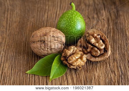 Young and old walnuts on wooden background.