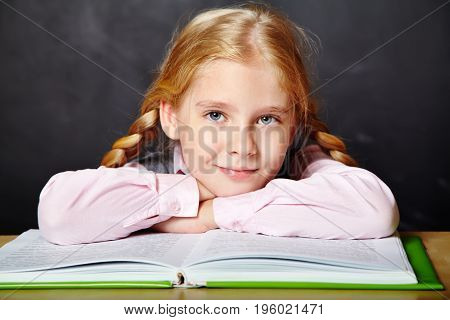 girl reading a book. School and education. a child learns in school