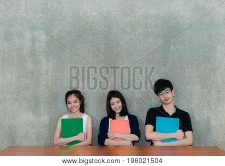 Young Students Group Smile Hugging School Folders Booke on Table and Gray Background in Education Campus University