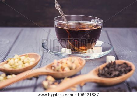 diferent dry tea in a three wooden spoons and cup of tea