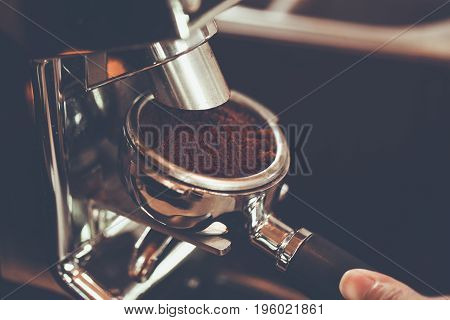 Hand of Barista put a portafilter to espresso machine for brewing coffeecolor vintage style Thailand