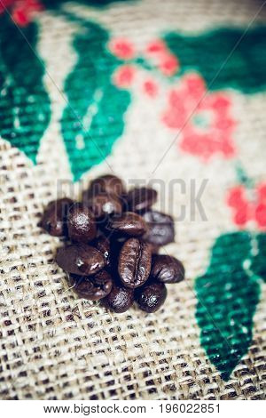 Top view of coffee beans mediam rosted closeup shotBackground Sack of coffee beans Screen picture coffee tree and red seed Colour retro style Thailand