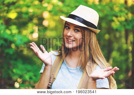 Portrait of a woman in the forest with a backpack and hat