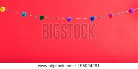 Red background with decorative pom pom border