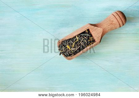 An overhead photo of a scoop of black tea leaves with flower petals, shot from above on a teal blue texture with a place for text