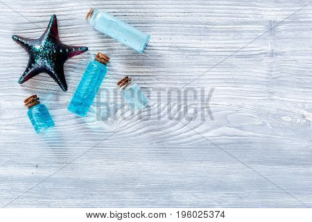 Sea cosmetics. Sea salt, blue clay and lotion on wooden background top view.